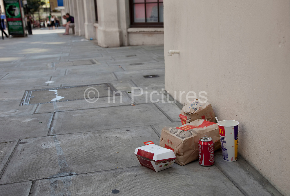 """Littering. Discarded fast food packaging in London. McDonalds trash. A tourist has written """"This is a present from Spain"""" on the rubbish."""