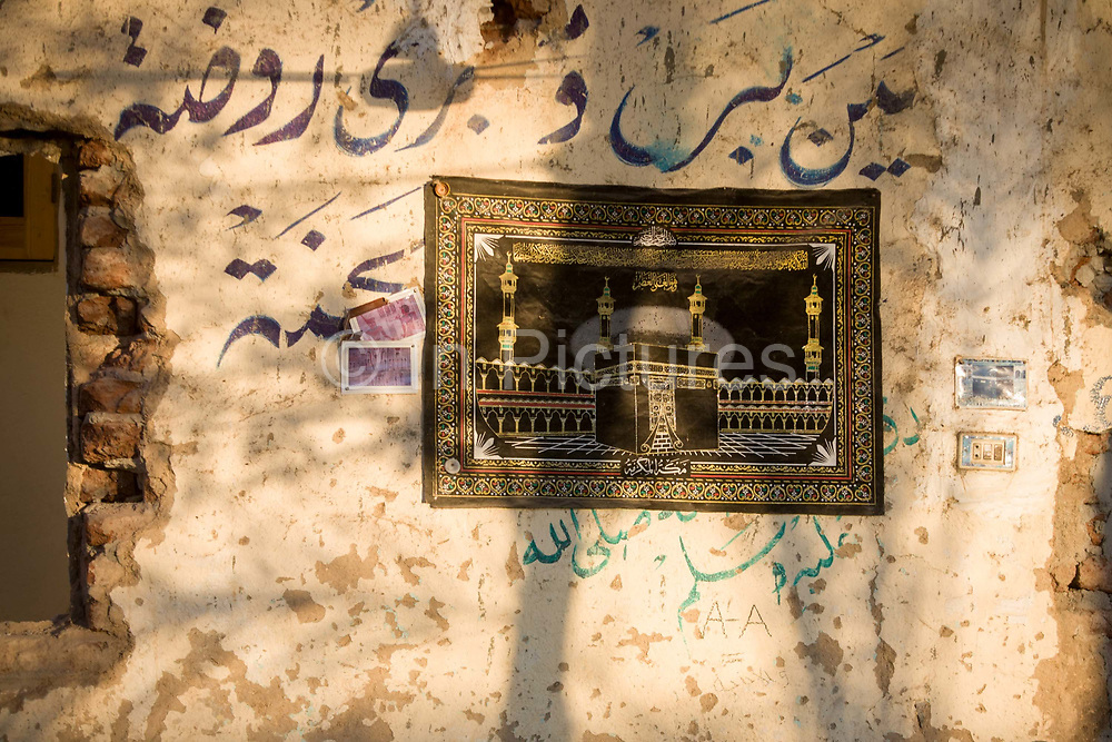An embroidery showing the kaaba shrine in Mecca on an exterior wall in the village of Bairat on the West Bank of Luxor, Nile Valley, Egypt. The Kaaba, or Kaʿbah, is a small shrine near the centre of the Great Mosque in Mecca and considered by Muslims everywhere to be the most sacred spot on Earth. Islam in Egypt is the dominant religion in a country with around 80 million Muslims, comprising 94.7% of the population, as of 2010. Almost the entirety of Egypt's Muslims are Sunnis, with a small minority of Shia and Ahmadi Muslims. The latter, however, are not recognised by Egypt.