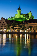 Munot Castle reflects in the Rhine River after sunset, in Schaffhausen, Switzerland, Europe.  Schaffhausen was founded where trading ships had to set anchor because Rhine Falls blocked further travel. The Munot, Schaffhausen's iconic circular fortress, was built by forced labor in 1564-1589 after the religious wars of the Reformation.