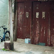 Bicycle standing in front of worn down building in Tai O fishing village, Lantau Island.