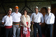 UNK UNK the owner of the restaurant and his wife with shawl in traditional clothing and Albanian hat, white with round top tied with an orange yellow cloth and the staff waiters of the restaurant. Tradita traditional restaurant, Shkodra. Albania, Balkan, Europe.