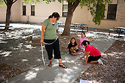 Lovington schools math intervention specialist Maggie Clayton works with students using chalk on the sidewalk to help students understand unit measurements. The schools in Lea County are using Recovery and Reinvestement funds to pay for much needed teachers and specialists like Clayton, who also coaches other teachers to help them come up with better ways to involve the students.