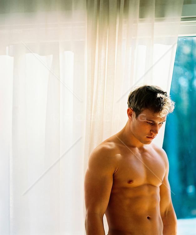 Good looking shirtless man at home