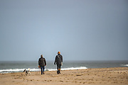 People walk their dogs alongside the sand gold beach of Bamburgh on Wednesday, March 17, 2021. Bamburgh is home to the most important Anglo-Saxon archaeological sites in the world, the Bamburgh Castle. (Photo/ Vudi Xhymshiti)