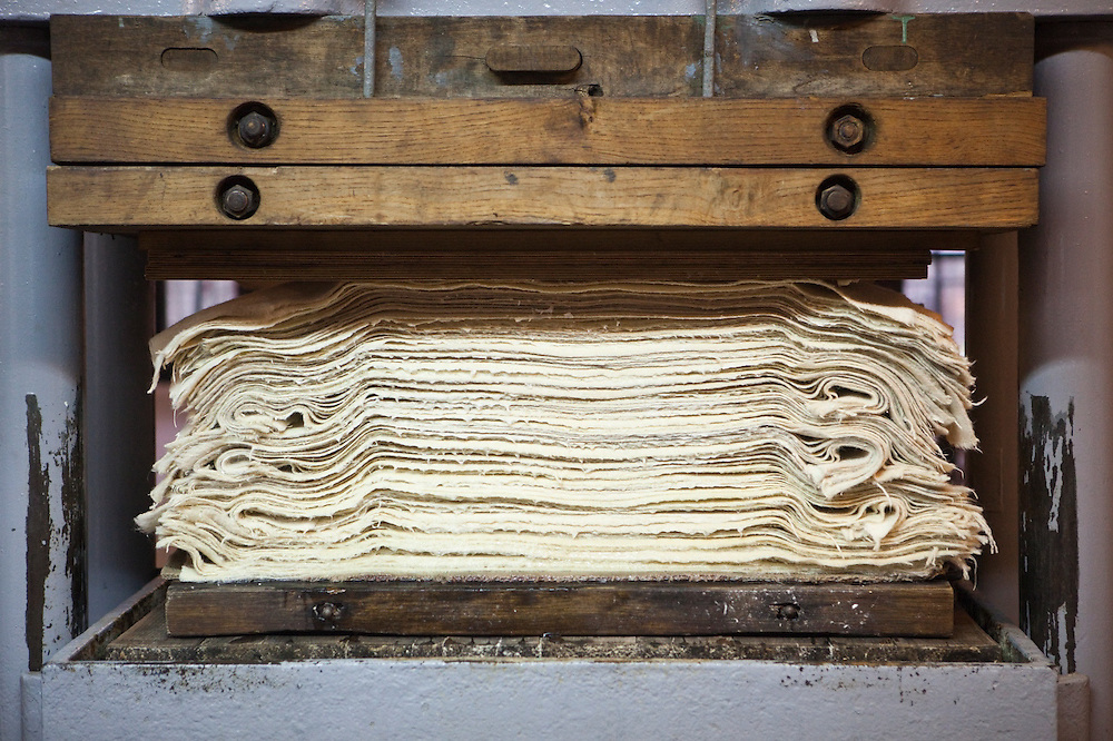 Freshly handmade paper is pressed to remove excess moisture at the historic Paper Mill in Duszniki-Zdroj, Poland.
