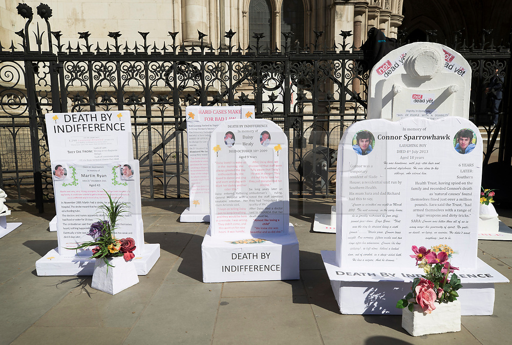 """© Licensed to London News Pictures. 01/05/2018. London, UK. Disability group 'The Distant Voices', which campaigns against euthanasia, erect grave stones outside the High Court as terminally ill man Noel Conway challenges the law on assisted suicide. Mr Conway, who has motor neurone disease, is asking judges to acknowledge his """"basic right to die"""". Photo credit: Peter Macdiarmid/LNP"""