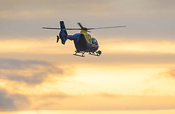 © Licensed to London News Pictures. 20/12/2018. London, UK. A police helicopter hovers over the runway at Gatwick airport. Flights have been cancelled and thousands of passengers have been delayed after the airport closed due to two drones being spotted nearby. Photo credit: Peter Macdiarmid/LNP