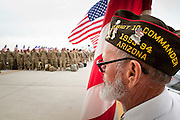 """15 JANUARY 2012 - PHOENIX, AZ:    A member of the VFW stands with a flag waiting for returing soldiers at the The 161st Air Refueling Wing of the Arizona Air National Guard in Phoenix. About 100 soldiers of A (Alpha) Company of the 422nd Expeditionary Signal Battalion (referred to as """"Alpha 4-2-2"""") of the Arizona Army National Guard returned to Arizona on Sunday, Jan. 15, following a nearly year-long deployment to Afghanistan. More than 10,000 Arizona Army and Air National Guard Soldiers and Airmen have been ordered to federal active duty in support of Operations Noble Eagle, Enduring Freedom, Iraqi Freedom, and New Dawn since September 2001. Approximately 200 Arizona National Guard Soldiers and Airmen are still serving on federal active duty overseas.  PHOTO BY JACK KURTZ"""