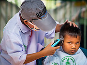 16 APRIL 2015 - BANGKOK, THAILAND:  A boy gets a haircut at a barber school that sets up on the platform at Hua Lamphong Train Station in Bangkok. Travelers get free haircuts and the barber students get to practice on real heads.    PHOTO BY JACK KURTZ