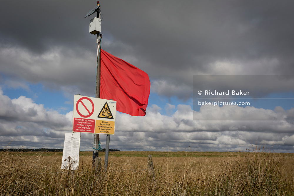 A red warning flag flies on the perimeter during military live firing at Otterburn Ranges, on 28th September 2017, in Otterburn, Northumberland, England. Twenty-three per cent of Northumberland National Park is owned by the Ministry of Defence and used as a military training area though they encourage as much access to the area as possible. Sometimes areas are cordoned off from the public for military exercises. Visitors are welcome outside of live firing times if no red flags are displayed. When military exercises are happening, red flags around the boundaries indicate restricted access. Visitors are told not to pick up, kick or remove any object and not to stray off the public rights of way or tarmac roads.