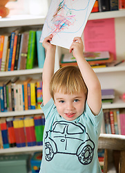 Boy holding a drawing above his head