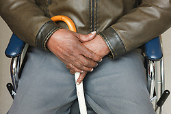 Visually-impaired wheelchair user with white stick at a resource for people with physical and sensory impairment.