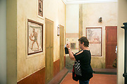 A woman takes a picture of a priapic satyr in the Secret Museum in Naples, Italy. The Gabinetto Segreto of Naples is the collection of erotic art in Pompeii and Herculaneum, held in separate galleries in the National Archaeological Museum, Naples, Italy, the former Museo Borbonico.