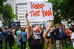 """© Licensed to London News Pictures. 29/05/2017. London UK. A demonstrator holds a sign aloft at an """"Anti-Hunting March"""" in central London, marching from Cavendish Square to outside Downing Street.  Protesters are demanding that the ban on fox hunting remains, contrary to reported comments by Theresa May, Prime Minister, that the 2004 Hunting Act could be repealed after the General Election.<br />  Photo credit : Stephen Chung/LNP"""