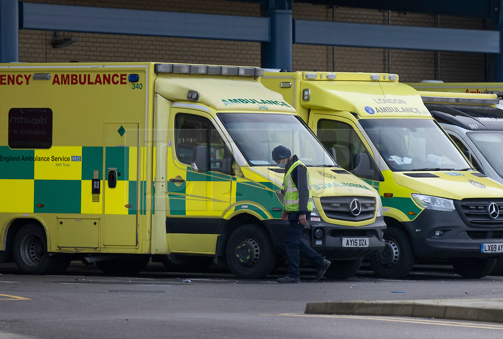© Licensed to London News Pictures. 30/12/2020. London, UK. A worker walks past a row of ambulances at The Queen's Hospital in Romford east London. The Medicines and Healthcare products Regulatory Agency (MHRA) has authorised the Oxford University Astra Zeneca coronavirus vaccine for use in the UK. Photo credit: Peter Macdiarmid/LNP
