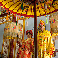 Tourists pose for photographs dressed in traditional Vietnamese  royal court costumes of king and queen, while visiting the Imperial City complex, Huế, Vietnam. The Imperial City is a UNESCO World Heritage Site.
