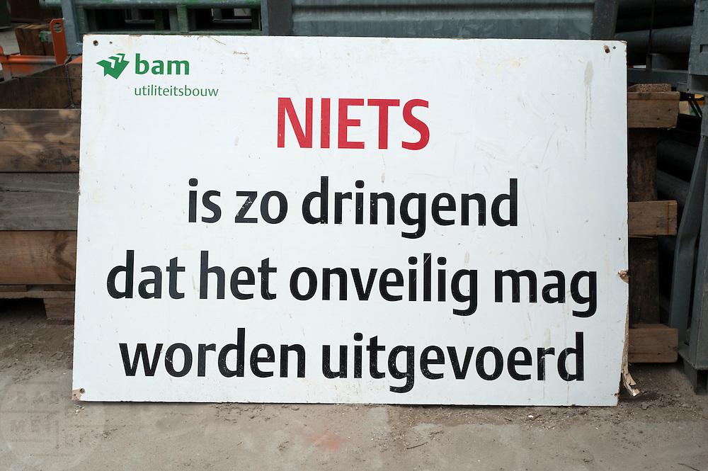Een bord bij een bouwplaats van de BAM wijst op het nut van de veiligheidsmaatregelen.<br /> <br /> A sign is warning to do the job at the construction area safely.