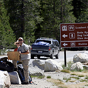 A couple hopes to hitch a ride out of Yosemite National Park after backpacking.
