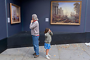 A man and young girl stand near WM Turner's 'Fighting Temeraire' and 'Seaport with the Embarkation of Saint Ursula' by Claude Lorrain - some of the paintings placed outside the National Gallery in Trafalgar Square, on 26th August 2021, in London, England.