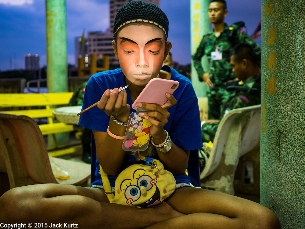 15 OCTOBER 2015 - BANGKOK, THAILAND:  A Chinese opera performer puts on her make up before performing at the Vegetarian Festival at the Joe Sue Kung Shrine in the Talat Noi neighborhood of Bangkok. The Vegetarian Festival is celebrated throughout Thailand. It is the Thai version of the The Nine Emperor Gods Festival, a nine-day Taoist celebration beginning on the eve of 9th lunar month of the Chinese calendar. During a period of nine days, those who are participating in the festival dress all in white and abstain from eating meat, poultry, seafood, and dairy products. Vendors and proprietors of restaurants indicate that vegetarian food is for sale by putting a yellow flag out with Thai characters for meatless written on it in red. The shrine is famous for the Chinese opera it hosts during the Vegetarian Festival. The operas are free.   PHOTO BY JACK KURTZ