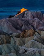 A shaft of sunrise light illumins Manley Beacon at Zabriski Point, in Death Valley National Park, California.