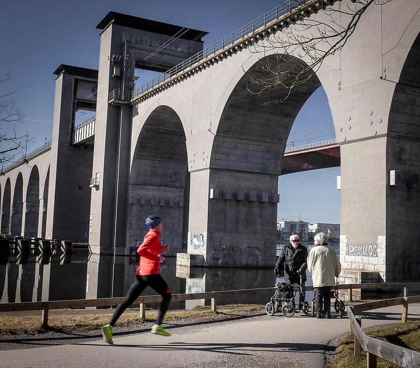 Nedanför Årstabron, järnvägen mot söder. De gamla med rullator stannar till för en pratstund, den unge löparen flyger förbi.