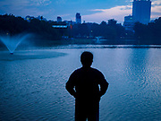 26 DECEMBER 2017 - HANOI, VIETNAM: A man stretches during his morning workout on the shore of Hoan Kiem Lake in the Old Quarter of Hanoi. Thousands of Vietnamese people line the lake front in the early hours of the morning to perform tai chi and other low impact aerobic workouts.  PHOTO BY JACK KURTZ