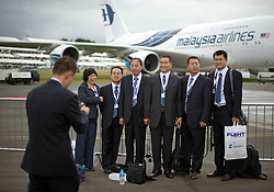 © London News Pictures. 09/07/2012. Farnborough, UK. Malaysian Businessmen and Businesswomen pose in front of a Malaysian Airlines Airbus A380 on day one of the Farnborough International Airshow, in Farnborough, Hampshire, UK on July 9, 2012. FIA is a seven-day international trade fair for the aerospace industry which is held every two years at Farnborough Airport . Photo credit: Ben Cawthra/LNP.