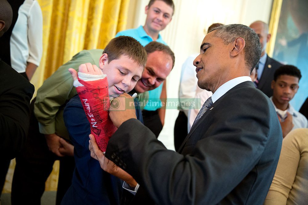 President Barack Obama signs a boy's cast as he visits with wounded warriors and their families in the East Room during a tour of the White House, Sept. 22, 2014. (Official White House Photo by Pete Souza)<br /> <br /> This official White House photograph is being made available only for publication by news organizations and/or for personal use printing by the subject(s) of the photograph. The photograph may not be manipulated in any way and may not be used in commercial or political materials, advertisements, emails, products, promotions that in any way suggests approval or endorsement of the President, the First Family, or the White House.