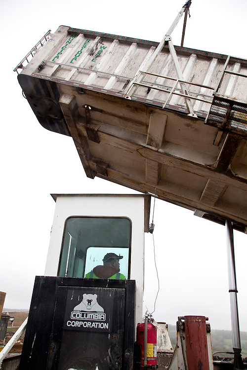 Crane operator lifts and dumps trailer of municipal solid waste transfer truck at open cell of sanitary landfill
