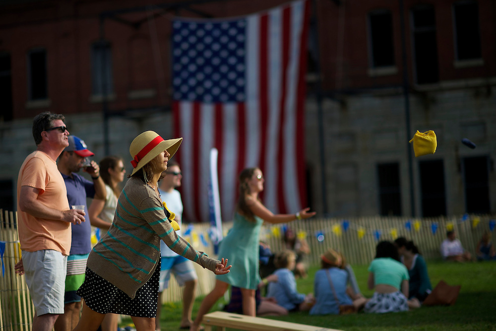 Attendees play bean toss during the Newport Folk Festival in Newport, RI on July 26, 2014. The three day festival was founded in 1959.