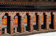 A row of  brightly painted prayer wheels at the state monastic school Dechen Phodrung Monastery. Thimpu, Druk Yul, Bhutan.   13 November 2007