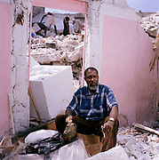 "Jocelyn Pierre, at the remains of his home, behind the US Consulate,  Port Au Prince. Jocelyn is retuning to rebuild his business and house.  He has four grown up children who all live in America but he wants to return to Haiti. He is a teacher, he is very proud of his son who is a surgeon in the Navy. ""I love Haiti more than myself. America is not my country.  We will overcome this. When you have faith, determination and sacrifice, you can do anything and we will bring you a brand new Haiti one day..Most of the problems are not to do with nature: the trees are still standing , the roads are OK but a brand new nine-storey hospital collapsed; why?"""