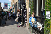 A woman sits outside a shop working on her laptop on Brick Lane, London<br /> Brick Lane was historically an poor area of Irish then Jewish and laterly Bangladeshi immigrants. Today it is the centre of a fashionale urban cultural revival.