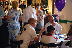 Guests sitting around table and standing at bar at wedding reception,