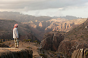 Local man looking at mountainous landscape at Dixsam with a view to the Hagier Mountains.  Socotra, Yemen