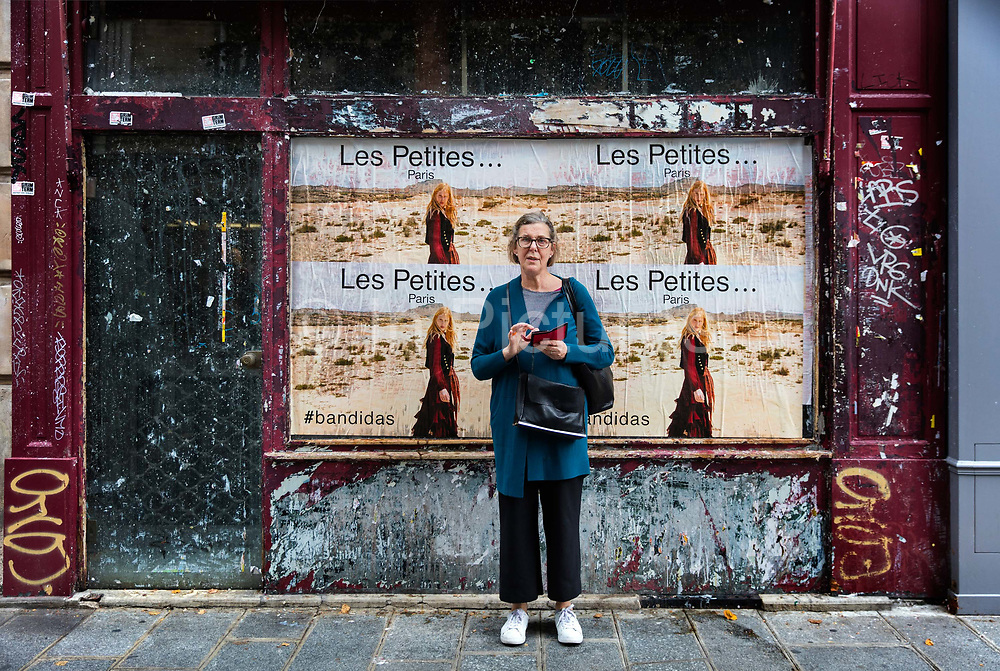 Touris holding a smart phone standing in front of an empty shop in the Marais district of Paris.