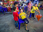 """06 DECEMBER 2015 - BANGKOK, THAILAND: Children watch a Chinese opera performance at the Ruby Goddess Shrine in the Dusit district of Bangkok. Chinese opera was once very popular in Thailand, where it is called """"Ngiew."""" It is usually performed in the Teochew language. Millions of Chinese emigrated to Thailand (then Siam) in the 18th and 19th centuries and brought their culture with them. Recently the popularity of ngiew has faded as people turn to performances of opera on DVD or movies. There are about 30 Chinese opera troupes left in Bangkok and its environs. They are especially busy during Chinese New Year and Chinese holidays when they travel from Chinese temple to Chinese temple performing on stages they put up in streets near the temple, sometimes sleeping on hammocks they sling under their stage.     PHOTO BY JACK KURTZ"""