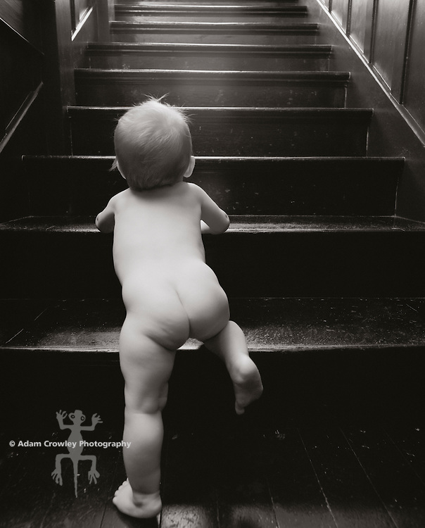 Baby (9-12 months) climbing stairs, rear view (B&W)