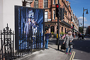 A muslim lady is about to cross the road, in front of a construction hoarding featuring a male with a bird of prey on his arm, on 23rd September 2016, in Mayfair, central London, England.