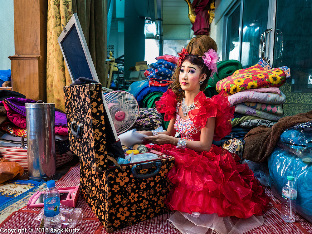 "30 JANUARY 2016 - NONTHABURI, NONTHABURI, THAILAND: A likay performer gets ready for a ""likay"" show at Wat Bua Khwan in Nonthaburi, north of Bangkok. Likay is a form of popular folk theatre that includes exposition, singing and dancing in Thailand. It uses a combination of extravagant costumes and minimally equipped stages. Intentionally vague storylines means performances rely on actors' skills of improvisation. Like better the known Chinese Opera, which it resembles, Likay is performed mostly at temple fairs and privately sponsored events, especially in rural areas. Likay operas are televised and there is a market for bootleg likay videos and live performance of likay is becoming more rare.     PHOTO BY JACK KURTZ"