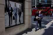 Man walks past a stylish clothing shop for businessmen people on a poster in the City of London. The businessman reads his copy of the Evening Standard newspaper and strides past very good-looking and stylish men wearing sharp suits - the latest in 2015 city fashion. The street is in the City of London, the capital's financial heart.
