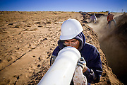 22 OCTOBER 2007 -- COYOTE CANYON, NM: KYLE GISHI, a member of a construction crew, installs water pipes on the Navajo Indian Reservation near Coyote Canyon. The project is a part of an effort by the tribe's government to bring potable water to the members of the Navajo Nation. More than 30 percent of the homes on the Navajo Nation, about the size of West Virginia and the largest Indian reservation in the US, don't have indoor plumbing or a regular supply of domestic water. Many of these homes have to either buy water from commercial vendors or haul water from public wells. A Federal study showed that the total cost of hauling water was about $113 per 1,000 gallons. A Phoenix household, in comparison, pays just $5 a month for up to 7,400 gallons of water. The lack of water on the reservation means the Navajo are among the most miserly users of water in the United States. Families that have to buy or haul water use only about 15 gallons of water per day per person. In Phoenix, by comparison, the average water use is about 170 gallons per day.  Photo by Jack Kurtz