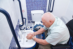 Male wheelchair user washing his hands in the sink of a wheelchair accessible WC,
