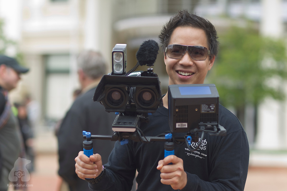 WELLINGTON, New Zealand, 25 October 2010.<br /> <br /> Filmmaker and digital visual effects artist Victor Huang holds a custom stereoscopic video camera during a gathering of thousands of supporters of film director Sir Peter Jackson. The rally held on Civic Square was attended by close to 3000 film industry workers, and wellingtonians in a show of support for the upcoming Hobbit films, a two-part prequel to the Lord of The Rings film trilogy...The Hobbit has been mired in industrial dispute involving New Zealand Actors' Equity (NZAE), an actors union, and the films' producers. NZAE's initial demand for a collective agreement was followed by a boycott of the films by the actors' union; a stance credited for threatening to derail the filming of The Hobbit in New Zealand and putting in jeopardy thousands of film industry jobs. Public opinion polls have overwhelmingly showed the unions are blamed by New Zealanders for the row that has threatened the $500 million USD project.