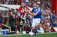 Jota of Brentford (l)and Cole Skuse of Ipswich Town compete for the ball. Skybet football league Championship match, Brentford v Ipswich Town at Griffin Park in London on Saturday 8th August 2015.<br /> pic by John Patrick Fletcher, Andrew Orchard sports photography.