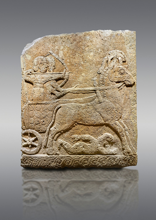 Hittite relief sculpted orthostat stone panel of Long Wall Limestone, Karkamıs, (Kargamıs), Carchemish (Karkemish), 900 - 700 B.C. Chariot. Anatolian Civilisations Museum, Ankara, Turkey<br /> <br /> One of the two figures in the chariot holds the horse's headstall while the other throws arrows. There is a naked enemy with an arrow in his hip lying face down under the horse's feet It is thought that this figure is depicted smaller than the other figures since it is an enemy soldier. The lower part of the orthostat is decorated with braiding motifs. <br /> <br /> On a gray background. .<br />  <br /> If you prefer to buy from our ALAMY STOCK LIBRARY page at https://www.alamy.com/portfolio/paul-williams-funkystock/hittite-art-antiquities.html  - Type  Karkamıs in LOWER SEARCH WITHIN GALLERY box. Refine search by adding background colour, place, museum etc.<br /> <br /> Visit our HITTITE PHOTO COLLECTIONS for more photos to download or buy as wall art prints https://funkystock.photoshelter.com/gallery-collection/The-Hittites-Art-Artefacts-Antiquities-Historic-Sites-Pictures-Images-of/C0000NUBSMhSc3Oo