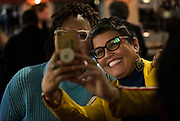 Ananda Mirilli takes a photo with an attendee at the Madison School Board election watch party at Robinia Courtyard in Madison, Wisconsin, Tuesday, Feb. 19, 2019.