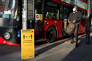 As the number of new Coronavirus cases in the UK climbs to 201,101, with UK deaths now standing at 30,076 - the highest recorded in Europe, passengers exits a bus towards a Transport For London TFL sign asking the public to maintain safe social distances while travelling on the capitals public transport during the continuing Covid lockdown, on 6th May 2020, in south London, England. Front doors on London buses are now disabled to avoid exposure of drivers to the virus, plus no fares are being taken on journeys to further avoid card reader contact.