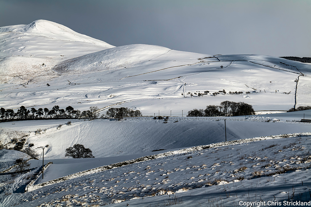 Hownam, Kelso, Scottish Borders, Scotland, UK. 10th February 2021. Deep snow and winter light pronounce the terracing of Hownam Rings in the Kale Valley.